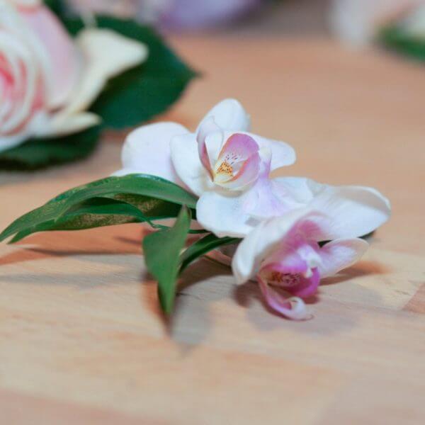 Knaphulsbuket med roser, liljer og orkideer