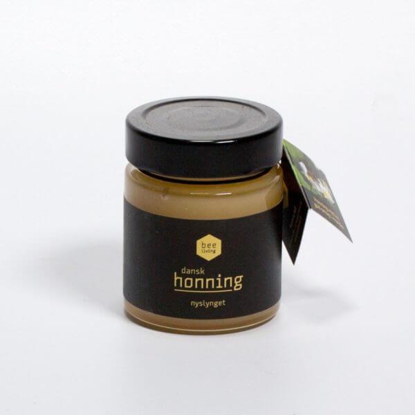 Honning vendt så man kan se seddel i elastik omkring låget